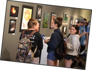 Photo courtesy of Spencer Myers. Students examine pieces in the exhibit.